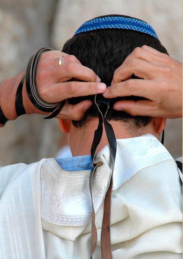 Rear view of man fixing head tefillin at the Western Wall in Jerusalem