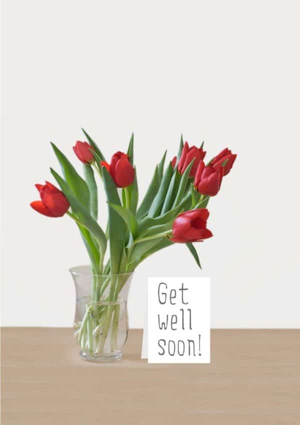 A bunch red tulips in a glass vase and a message on a card that reads 'Get Well Soon'