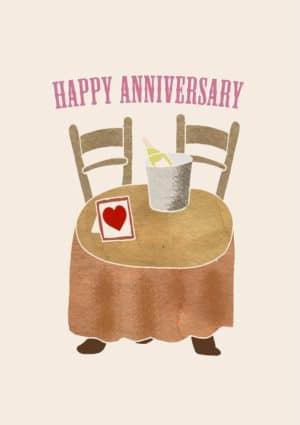 small round table covered with a tablecloth. There is an ice bucket and a bottle of champagne on the table. Also on the table is also a picture frame with an image of a red heart and text 'Happy Anniversary'