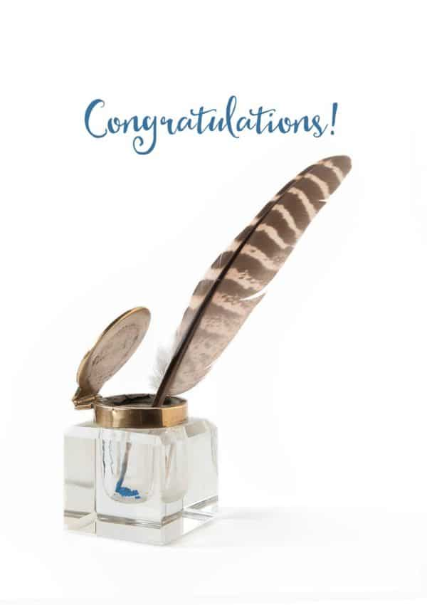 A congratulations card with an inkwell with a quill in the inkwell and a trace of blue ink, and text 'Congratulations'