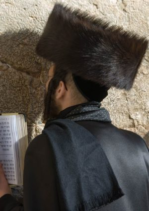A man wearing a fur hat or shtreimel praying at the Western Wall in the Old City of Jerusalem